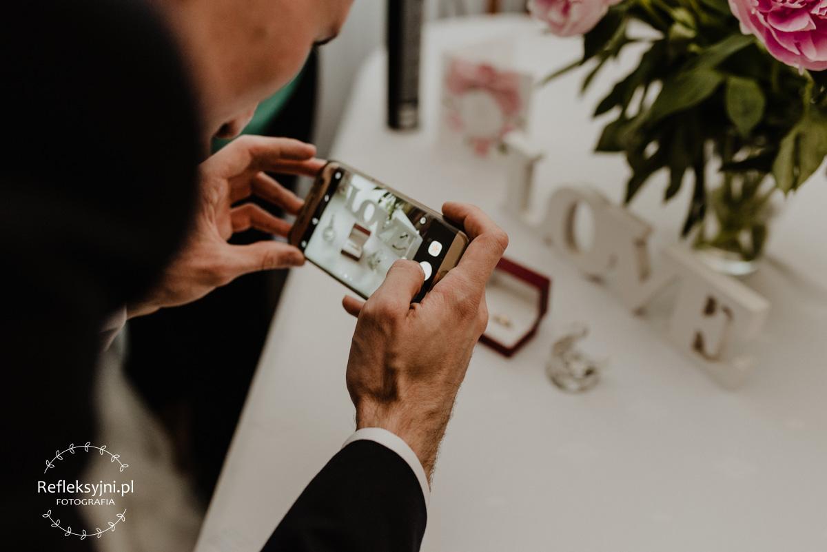 Pan Młody robi zdjęcie dodatków ślubnych