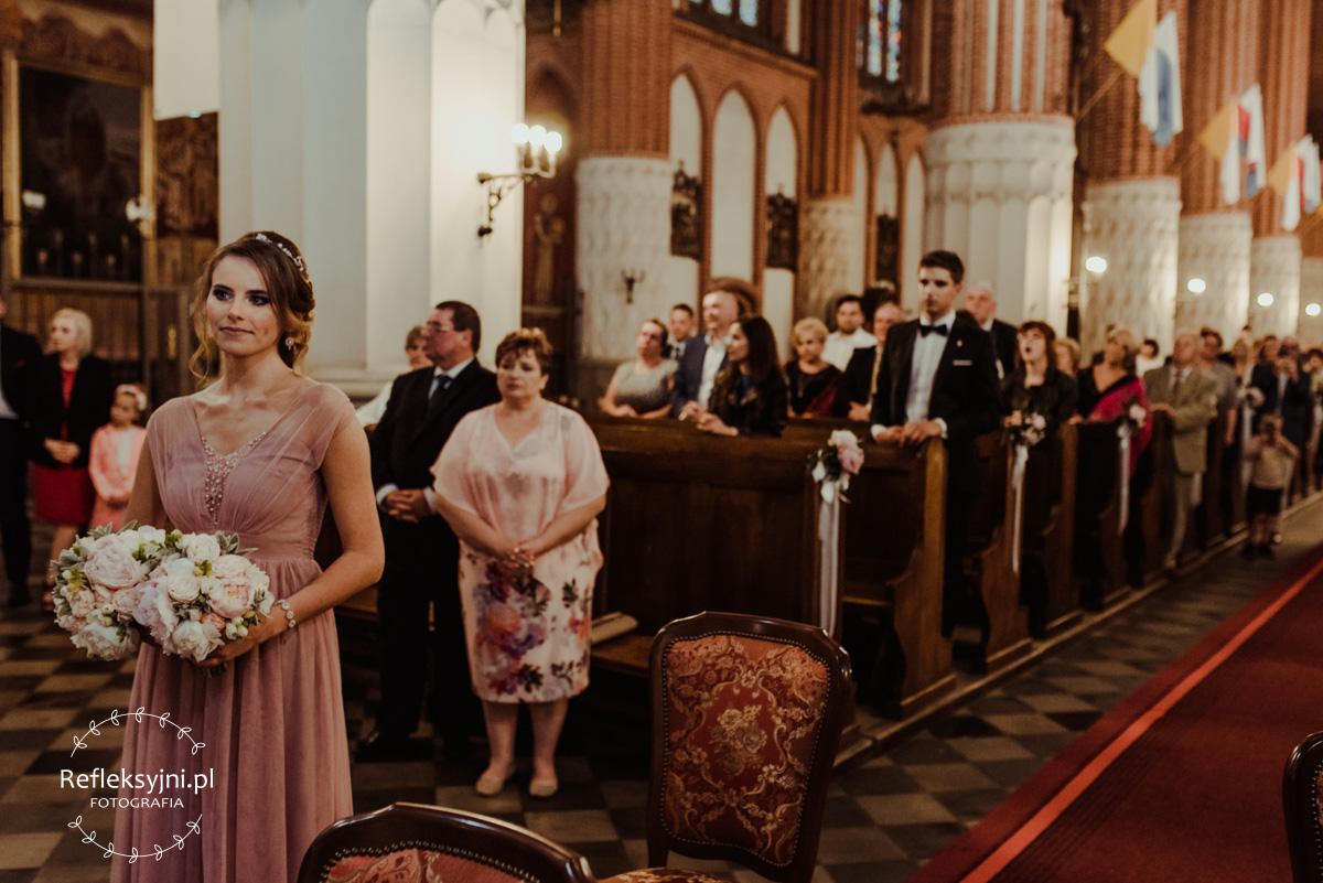Świadkowa trzyma bukiety ślubne podczas przysięgi