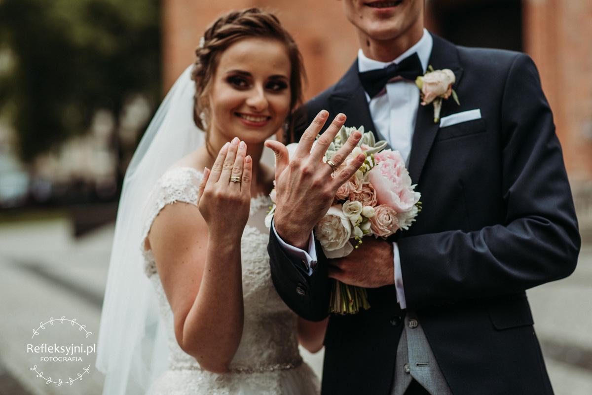Państwo młodzi pokazują obrączki ślubne