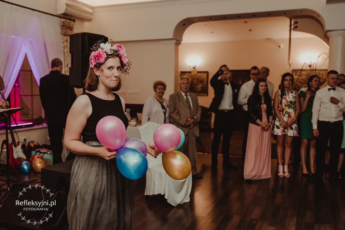 Pani z zespołu weselnego trzyma balony