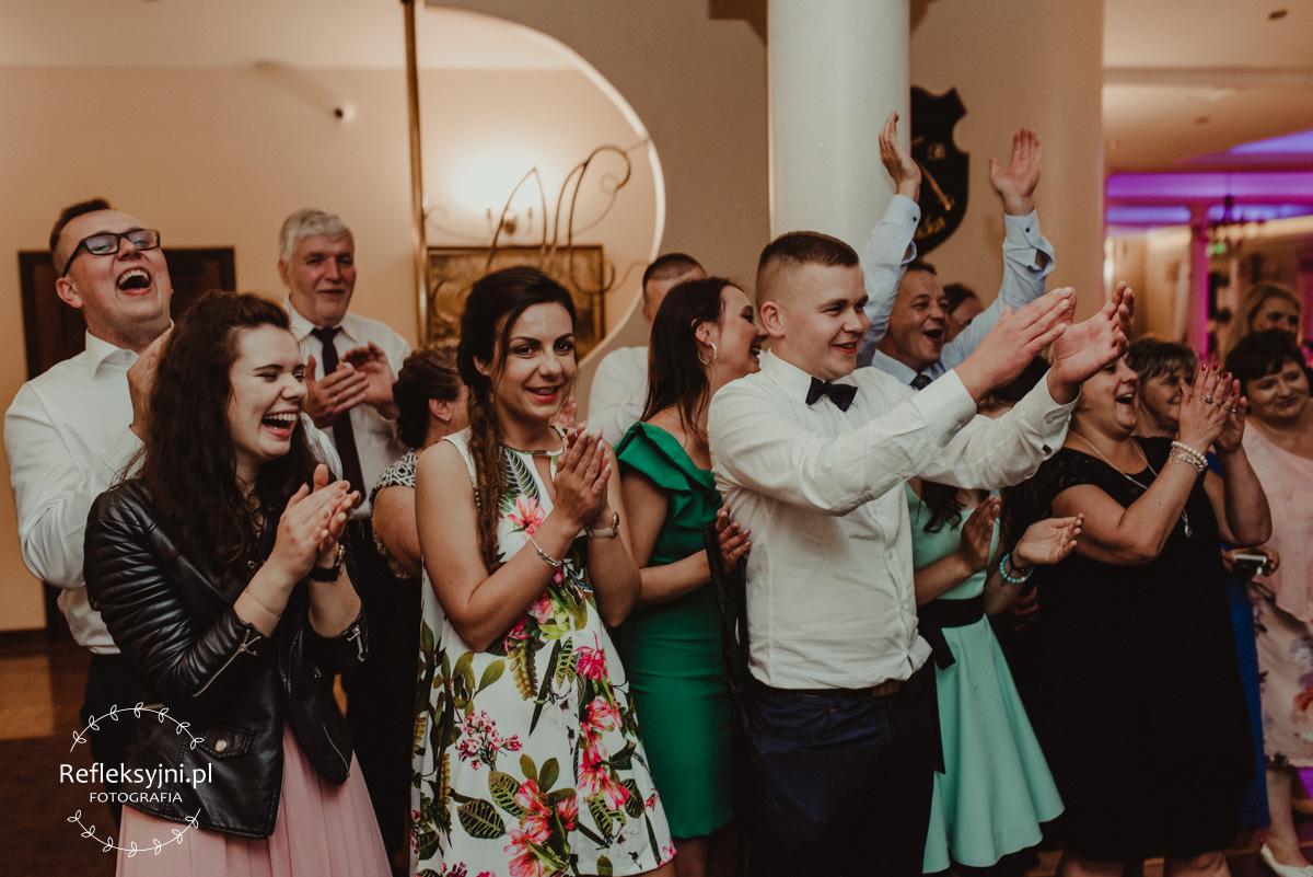 Tłum gości bijący brawo na weselu