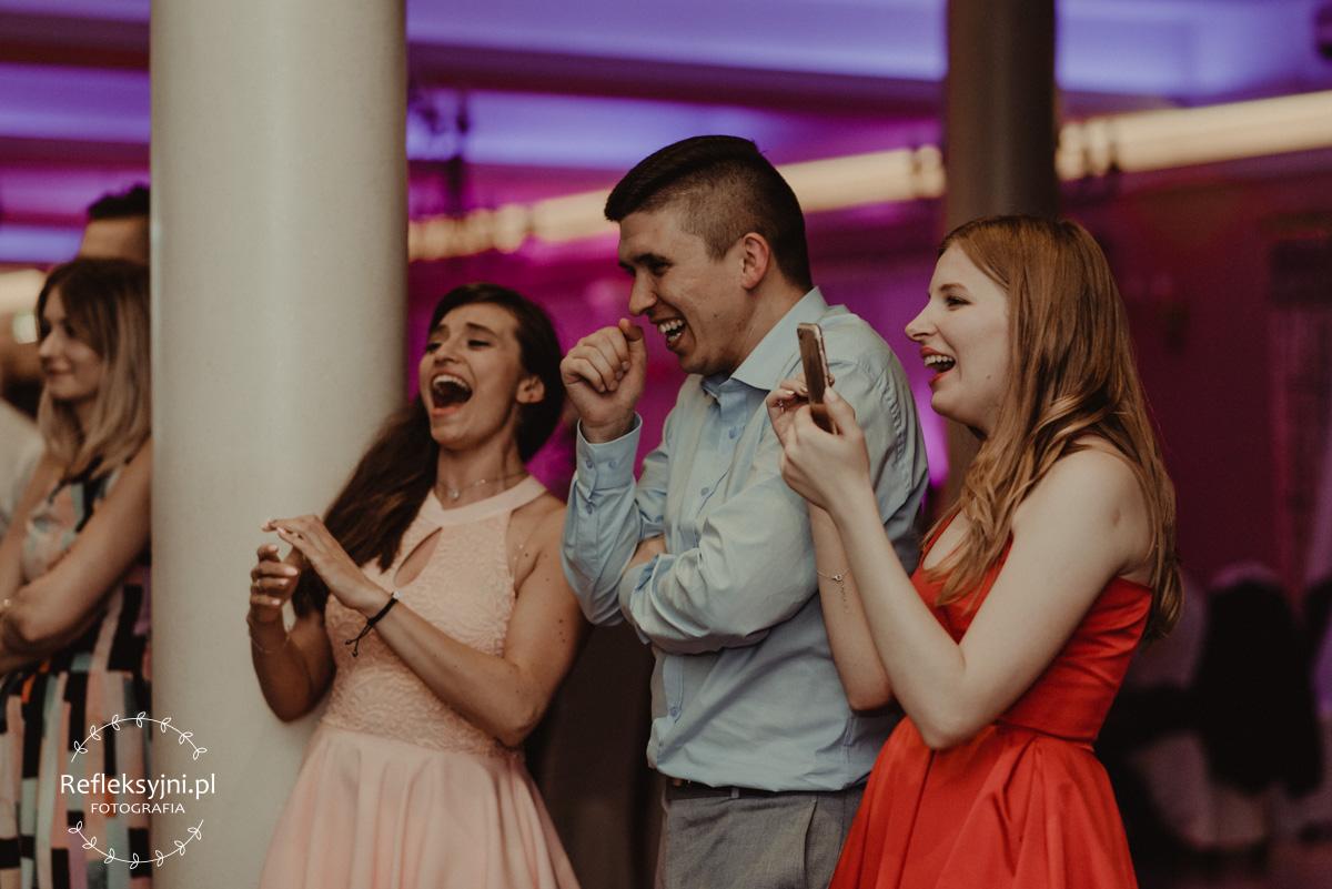 Trójka uśmiechniętych gości weselnych