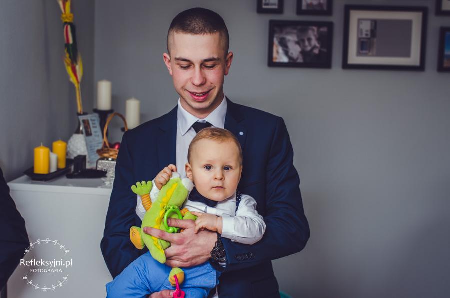 Dziecko z zabawką trzymane przez chrzestnego