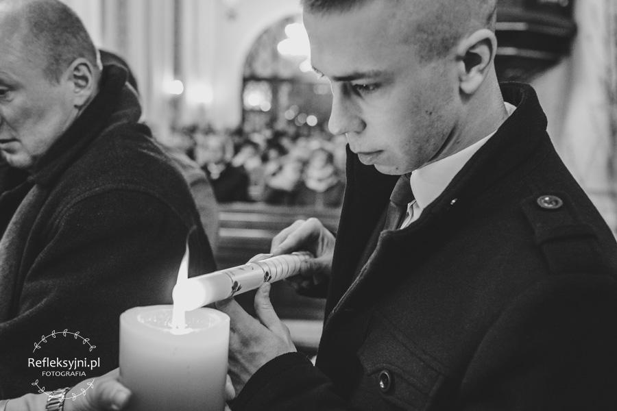 Chrzestny zapalający świecę Chrzcielną