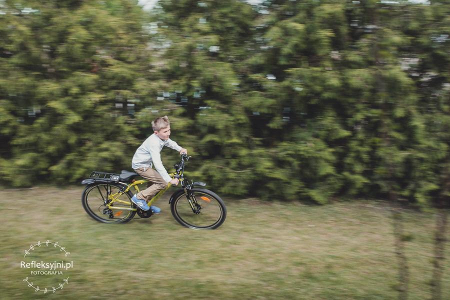 Chłopiec jadący na rowerze komunijnym
