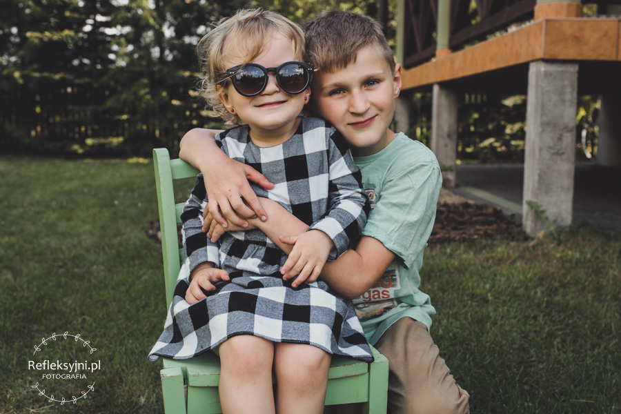 Dziewczynka siedząca na krześle w okularach przeciwsłonecznych z bratem