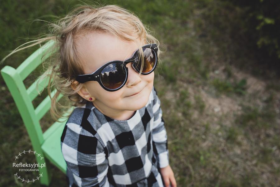 Dziewczynka siedząca na krześle w okularach przeciwsłonecznych