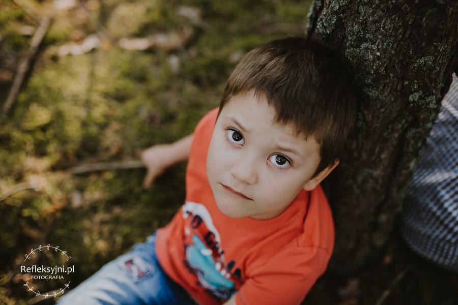 Chłopiec siedzący przy drzewie