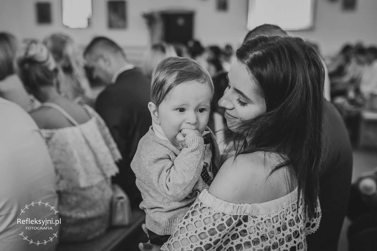 Mama trzyma dziecko na Chrzcie