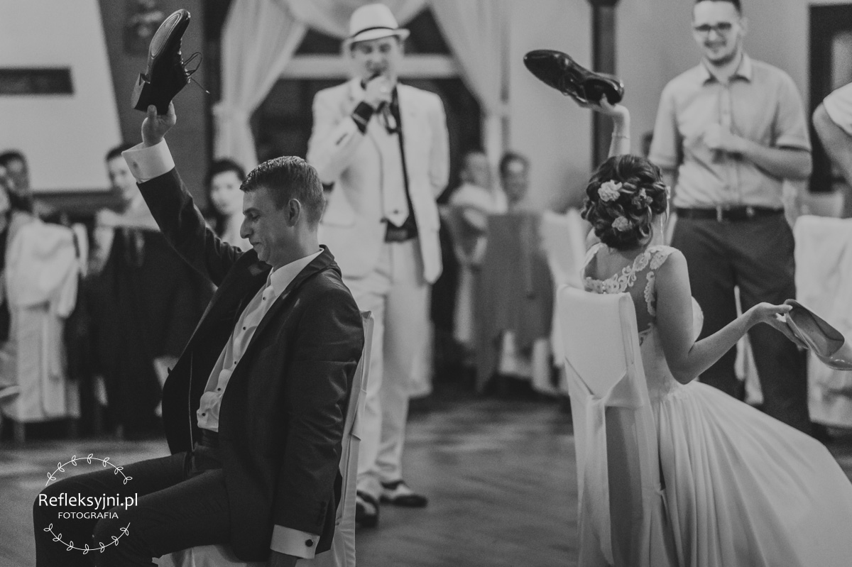 Państwo młodzi na zabawie weselnej trzymają buty