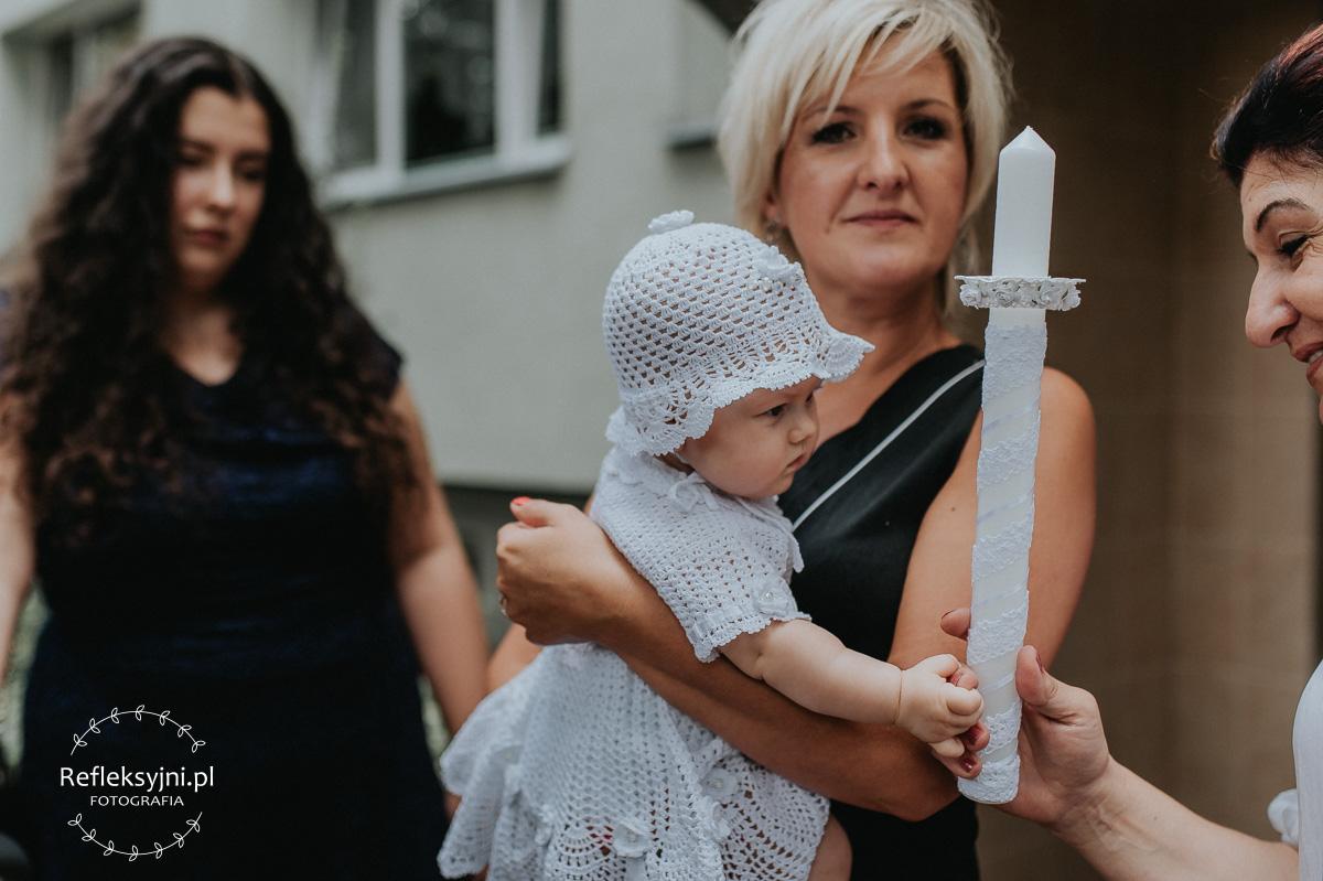 Dziecko trzymające świecę chrzcielną
