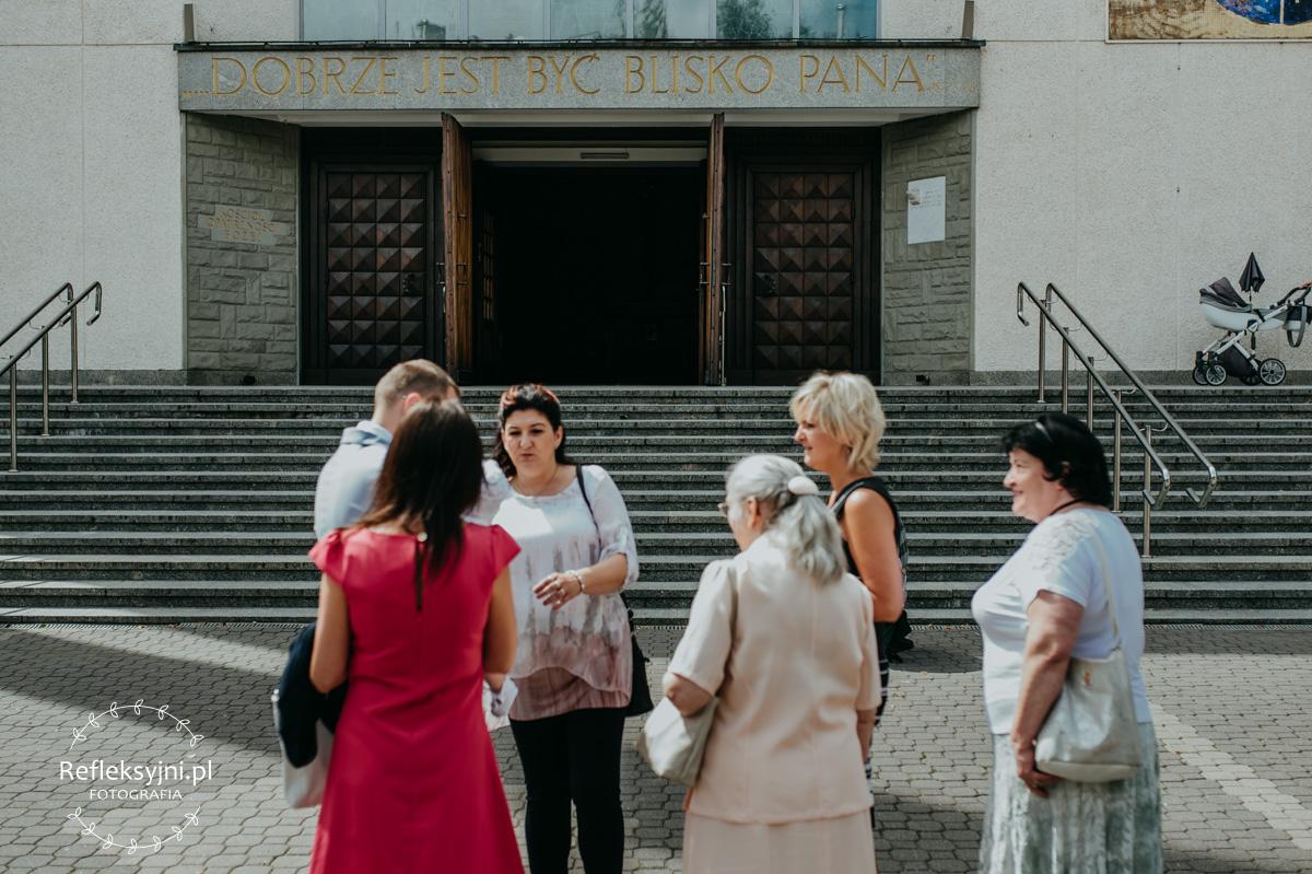 Grupa osób stojąca pod Kościołem