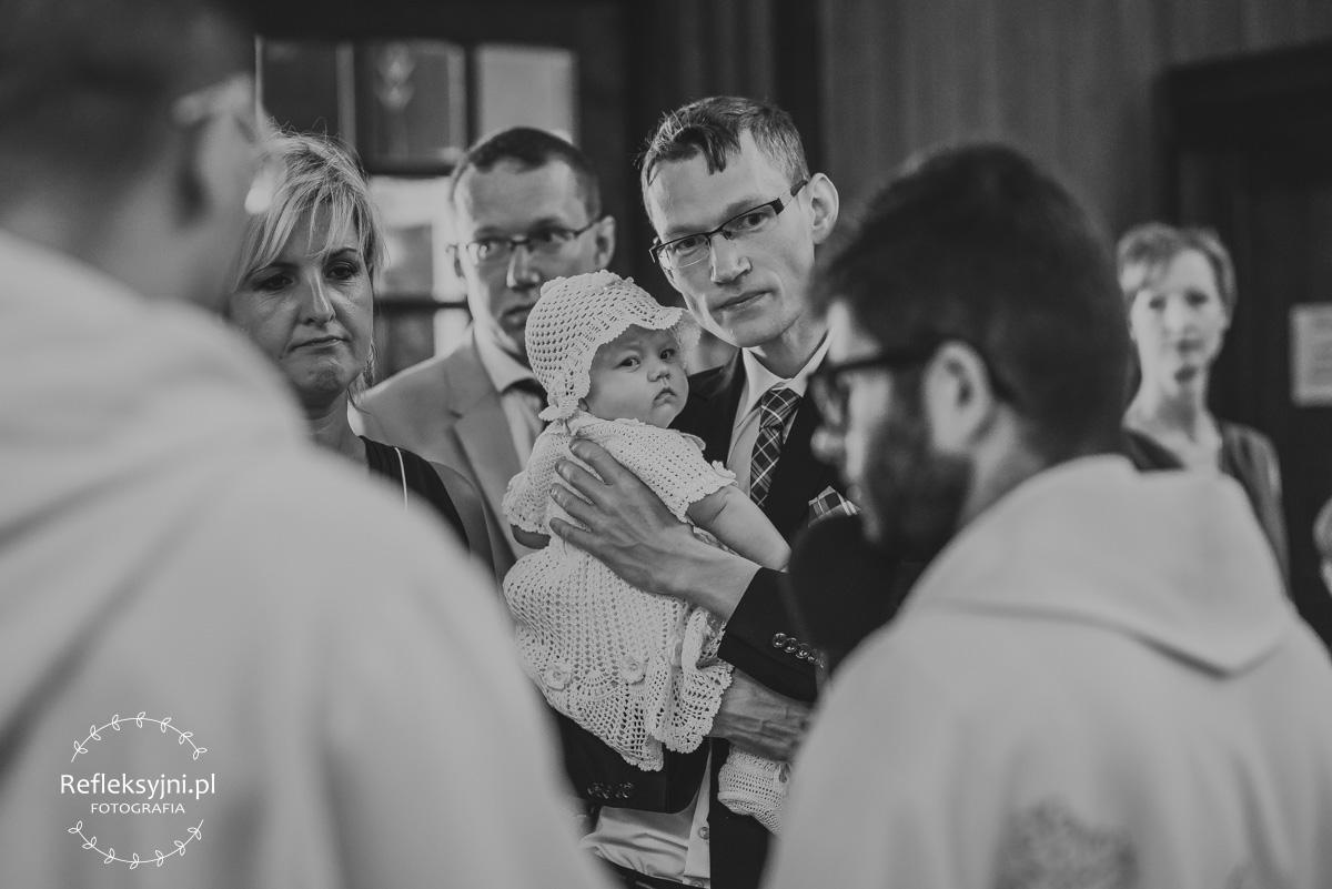 Tata trzymający na ramionach córkę