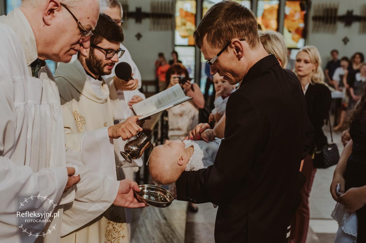 Ksiądz udzielający Chrztu dziecku