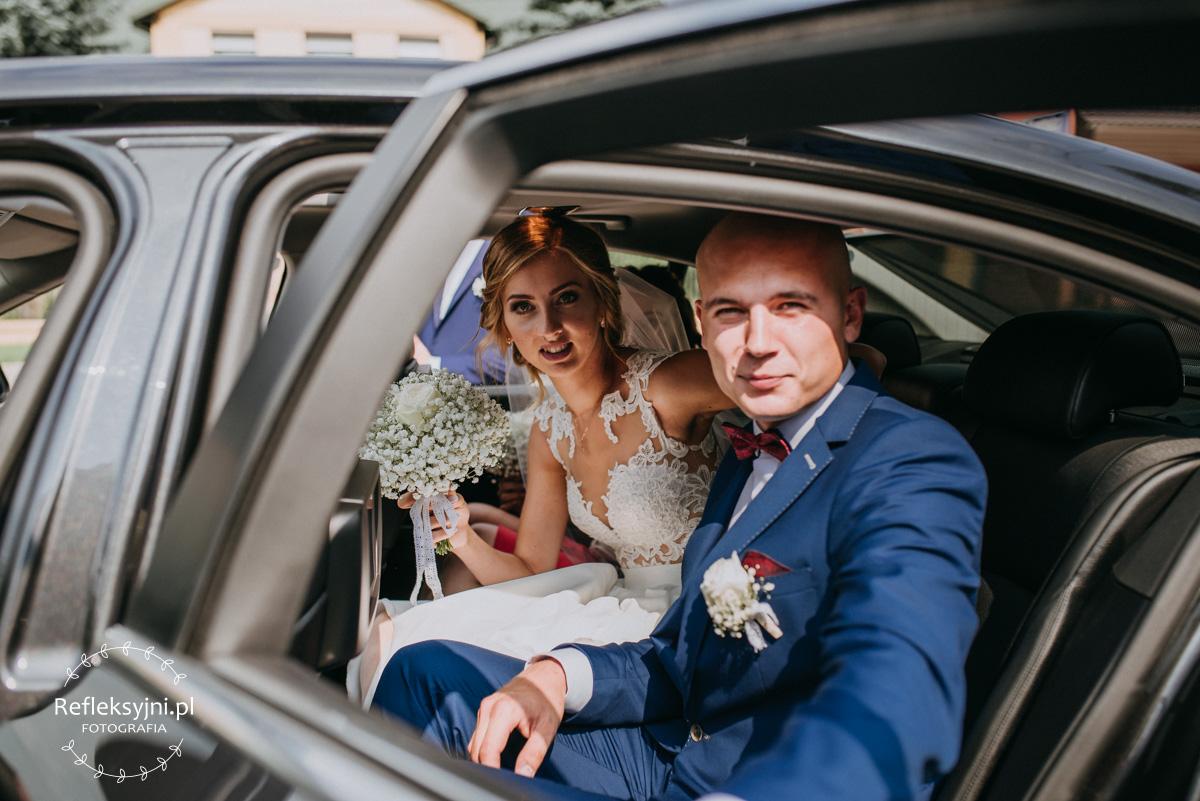 Państwo Młodzi siedzący w samochodzie weselnym