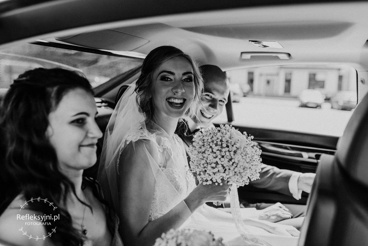 Państwo Młodzi śmiejący się w samochodzie ślubnym
