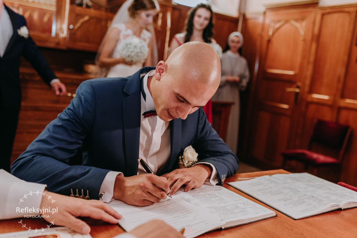 Pan Młody podpisuje akt ślubu