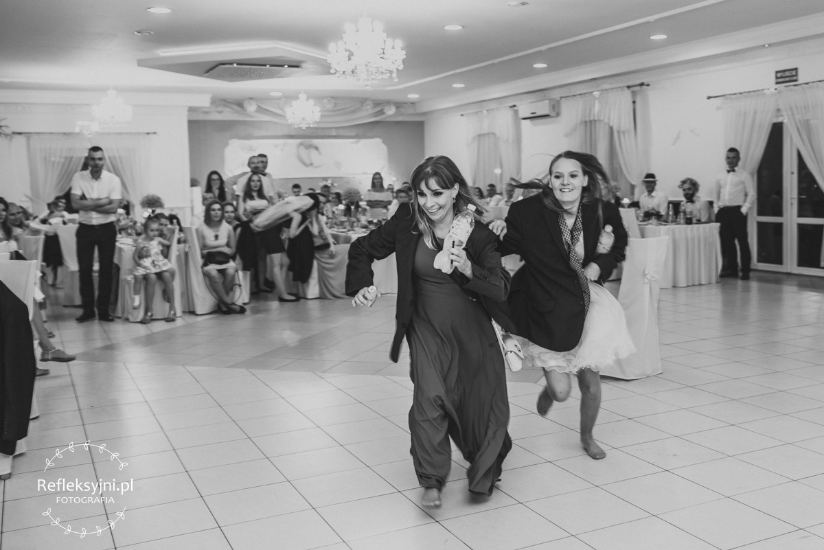 Dwie kobiety biegnące z butelkami na zabawie weselnej