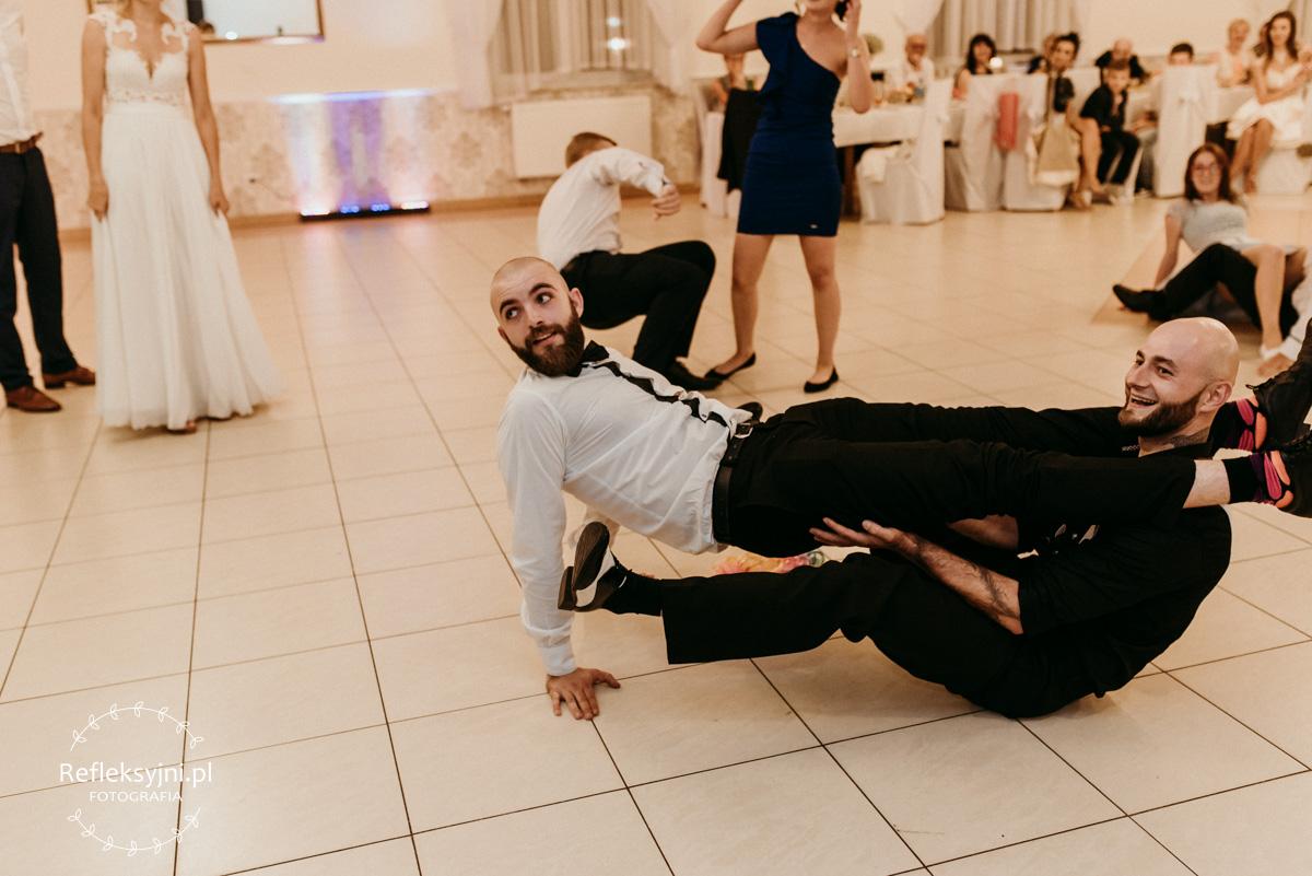 Panowie leżący na parkiecie podczas zabawy tanecznej
