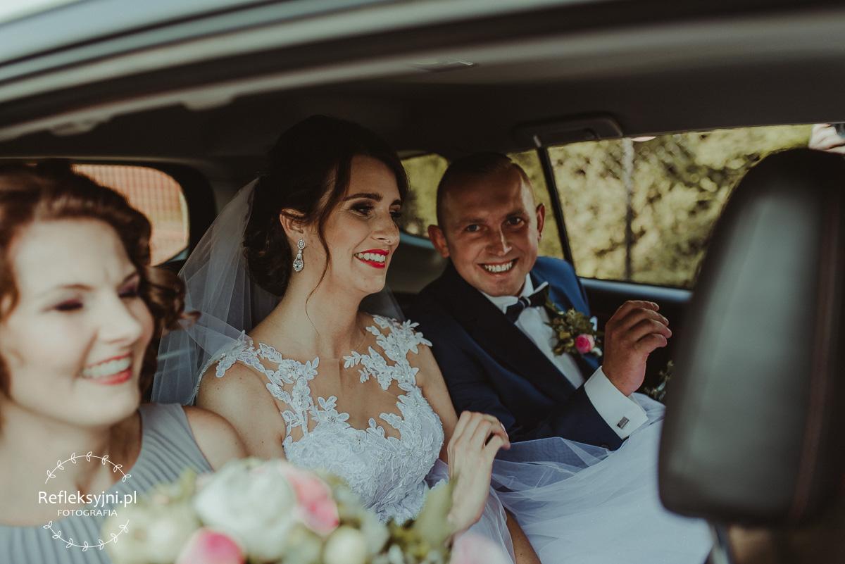 Panstwo Młodzi w samochodzie ślubnym