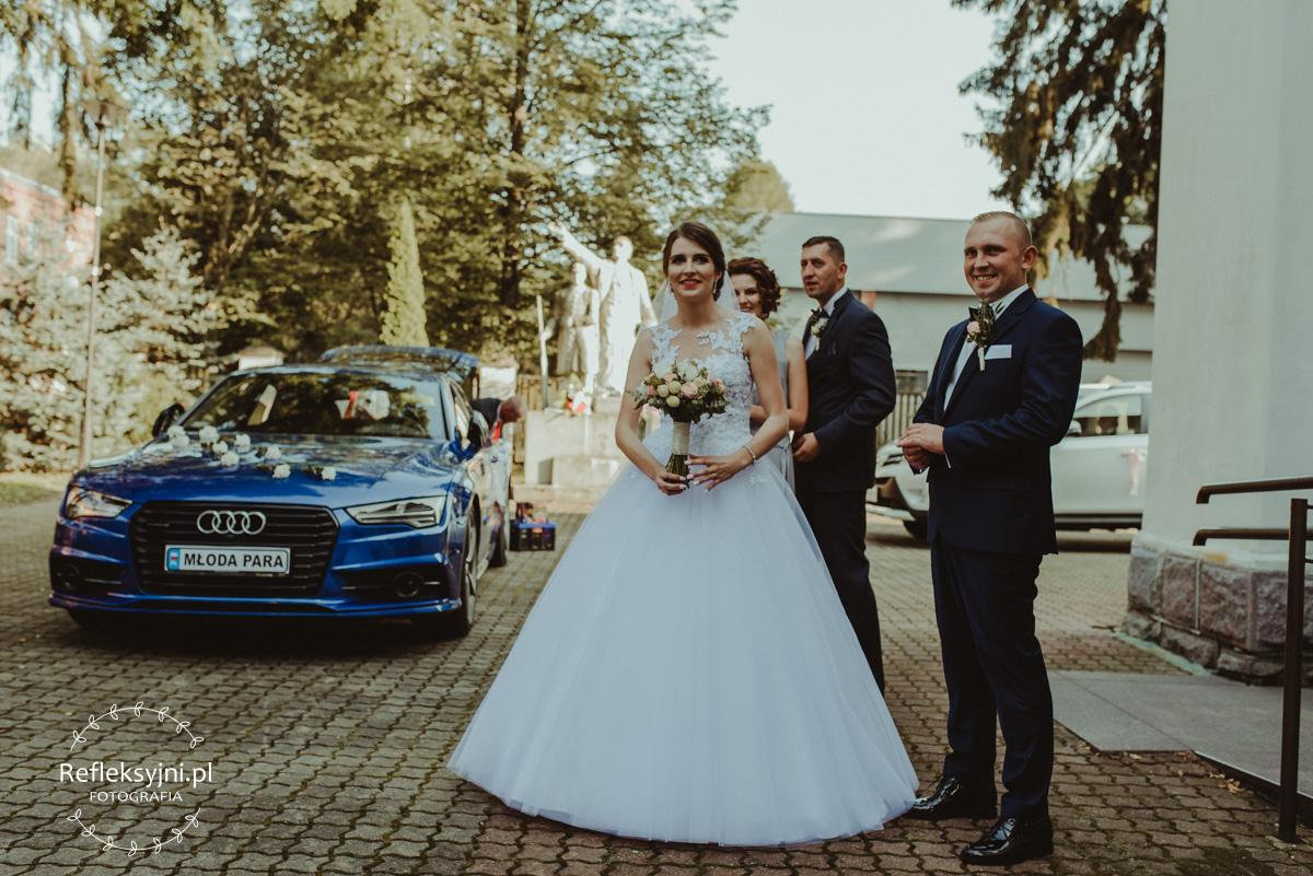 Państwo Młodzi przy samochodzie ślubnym