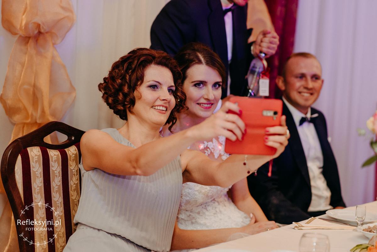 Świadkowa robi zdjęcie Pani Młodej telefonem