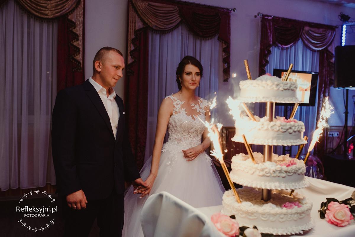 Państwo Młodzi przy torcie weselnym