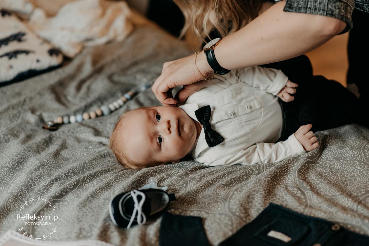Dziecko ubierane na Chrzest