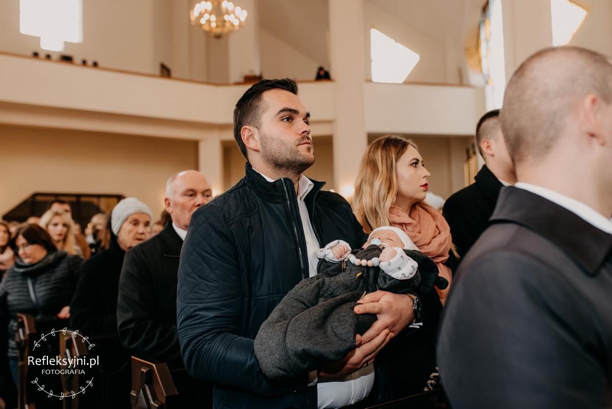 Dziecko trzymane przez tatę podczas Chrztu