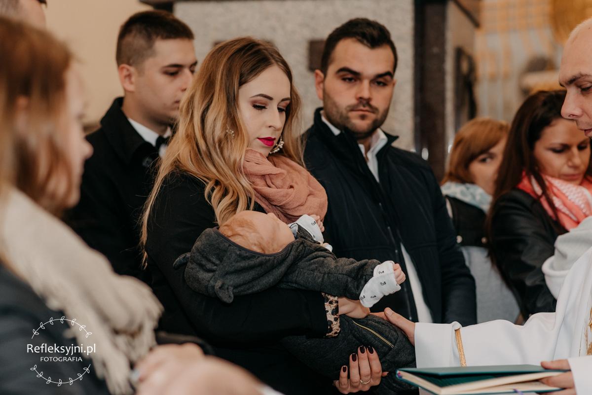 Dziecko trzymane przez mamę podczas Chrztu