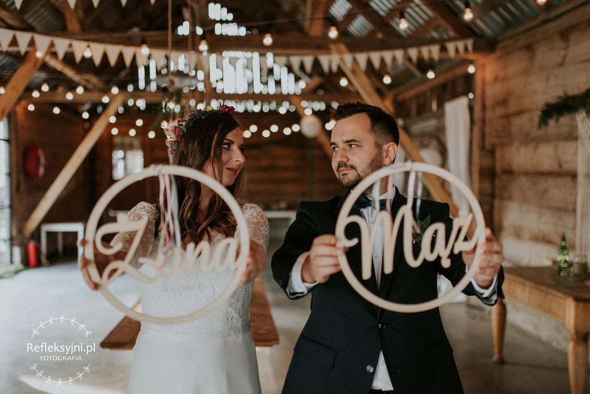 Państwo Młodzi z drewnianym napisem mąż i żona