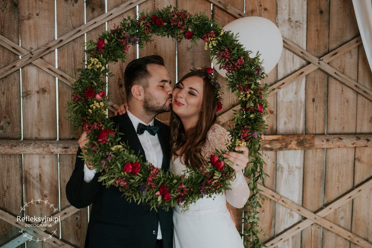 Państwo Młodzi całują się przy wieńcu ślubnym