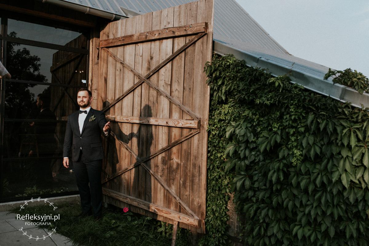 Pan Młody przy drewnianych drzwiach stodoły
