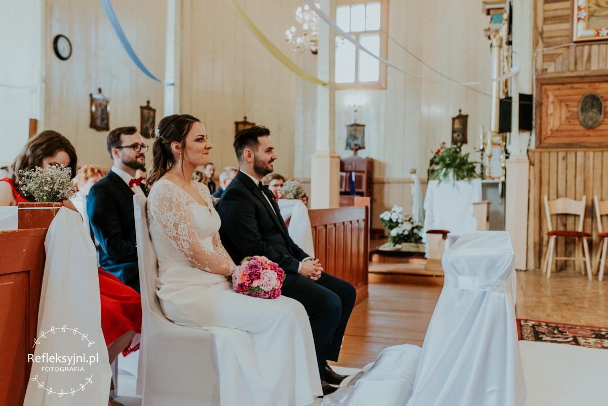 Siedzący uśmiechnięci Państwo Młodzi podczas Mszy Świętej