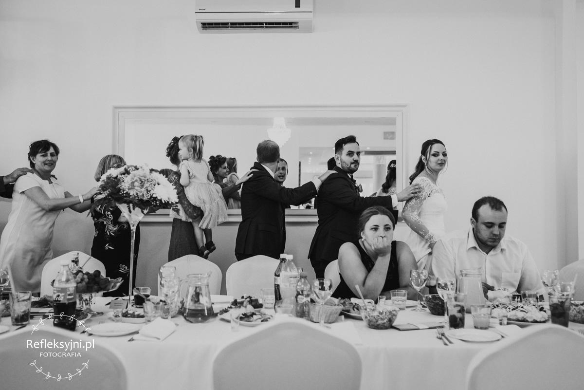 Goście weselni tańczą z Państwem Młodym