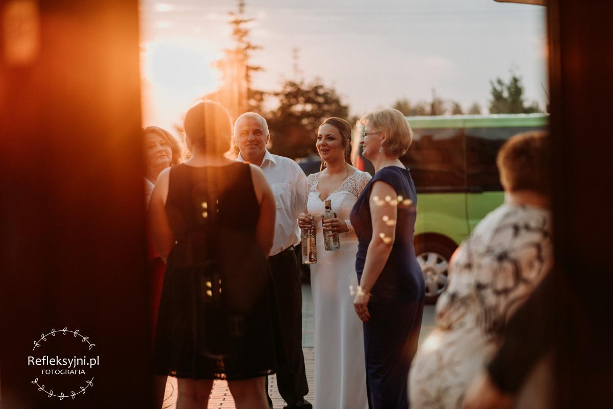 Pani Młoda z gośćmi na tle zachodzącego słońca przed salą