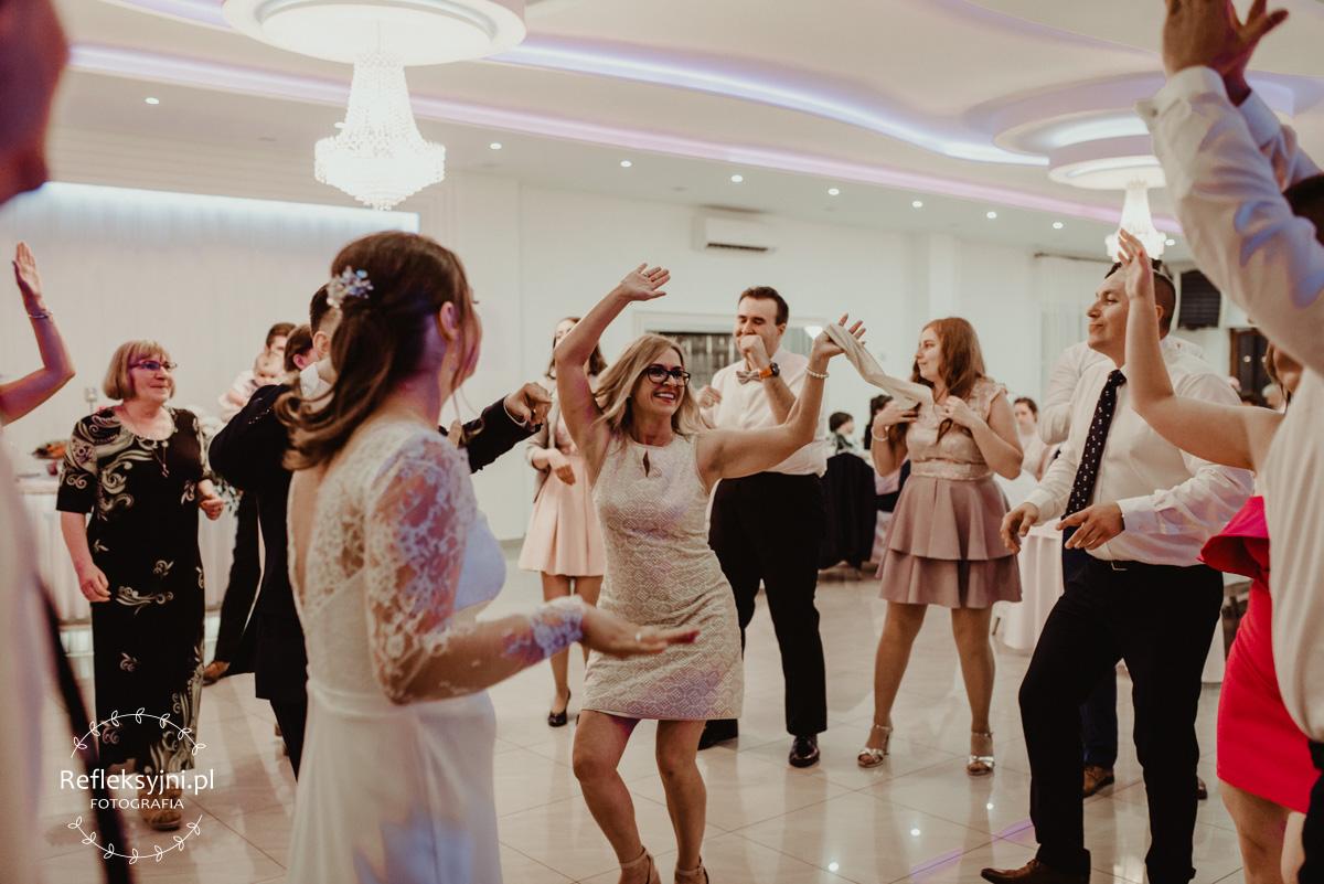 Goście tańczący w kółku na weselu