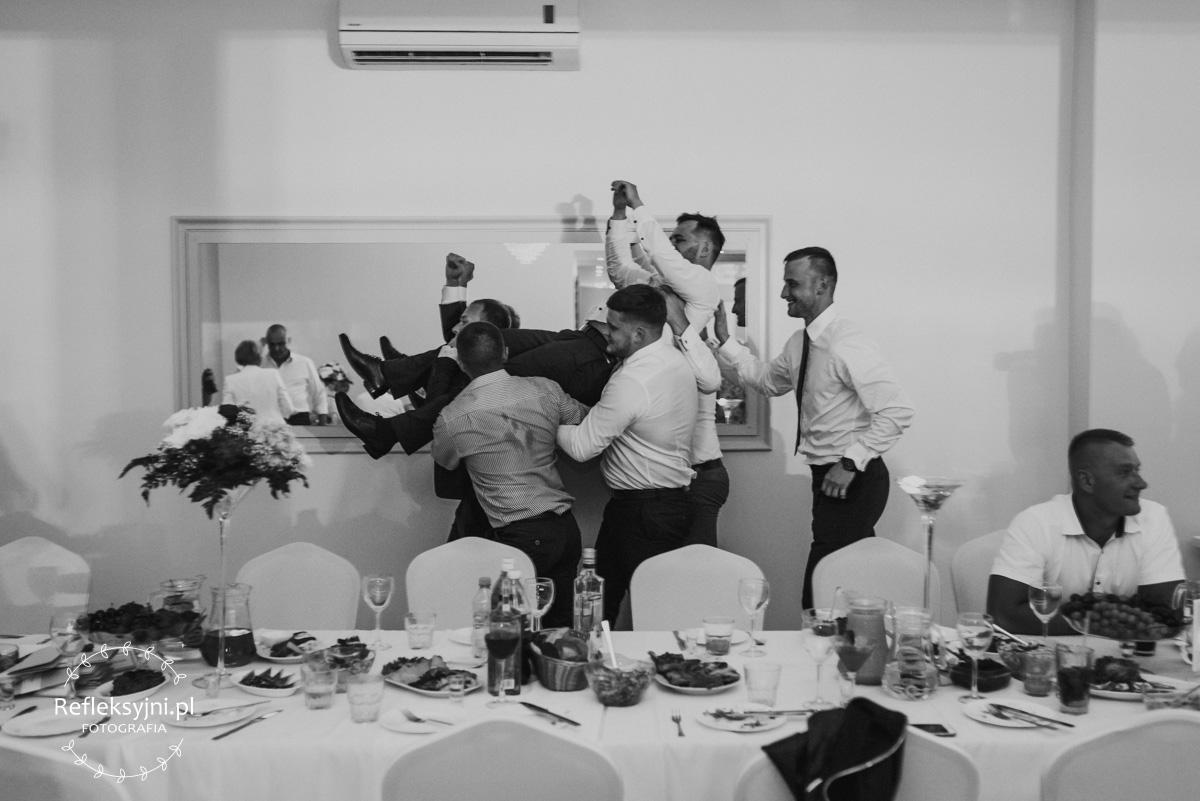 Pan Młody niesiony na ramionach gości weselnych