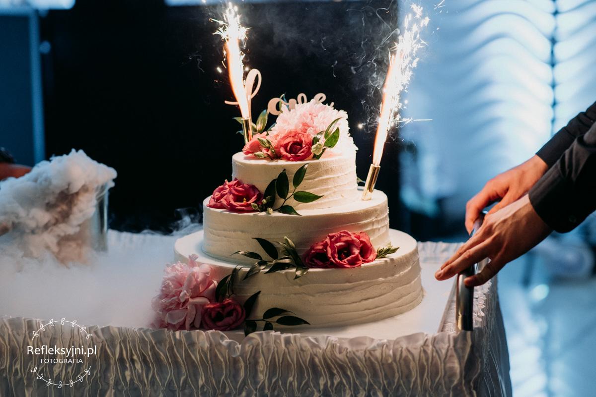 Tort weselny z zapalonymi świeczkami