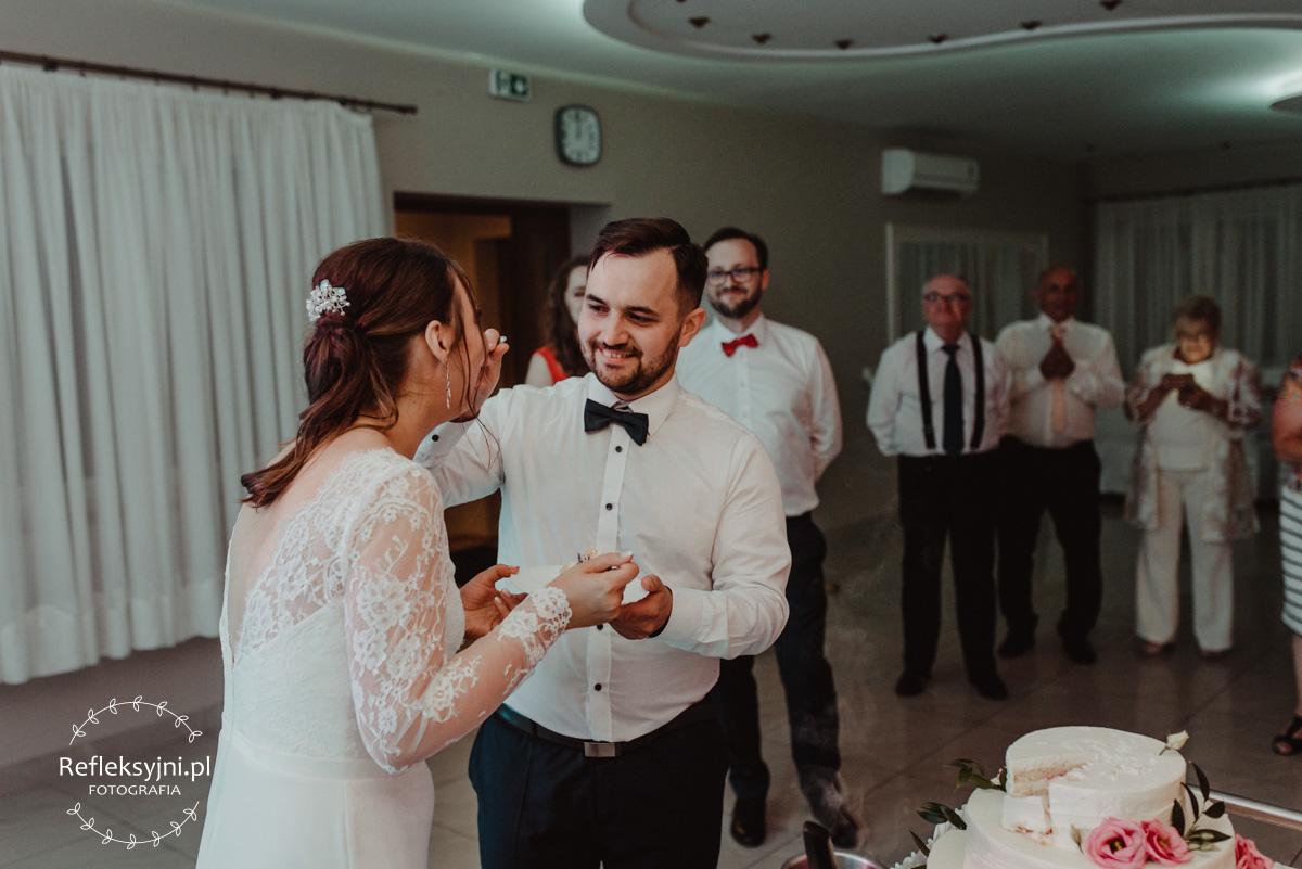 Państwo młodzi podczas konsumpcji tortu ślubnego