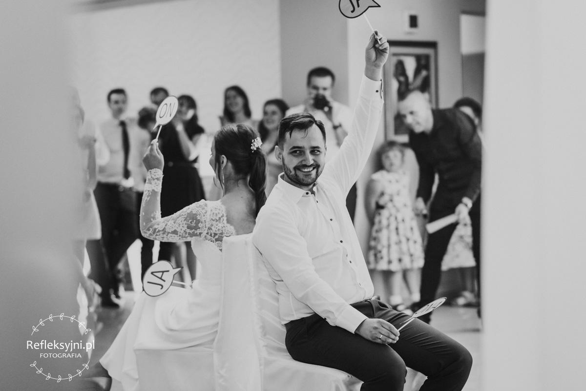Pan Młody siedzi na krześle podczas zabawy na weselnych oczepinach