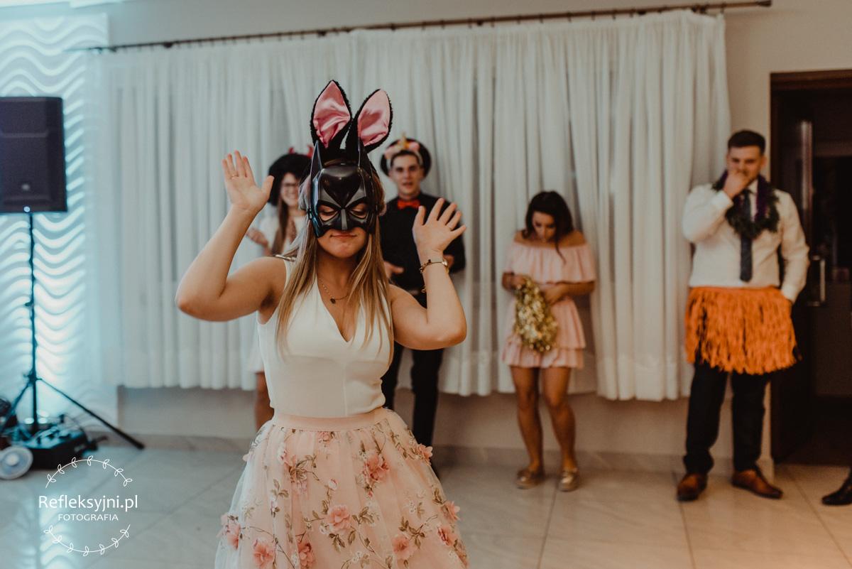 Zdjęcie przestawia gości weselnych na oczepinach w zabawnych maskach