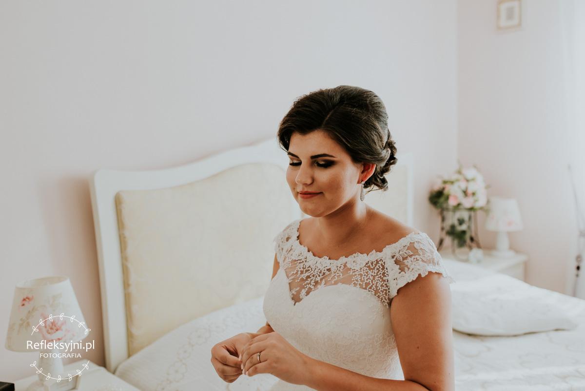 Pani Młoda zakładająca kolczyk podczas przygotowań do ślubu