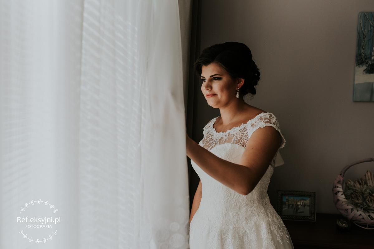 Pani Młoda podczas przygotowań do ślubu stojąca przy oknie