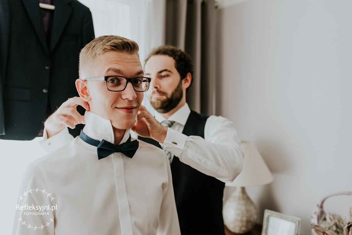 Pan Młody podczas przygotowań do ślubu ma zakładaną muchę przez świadka