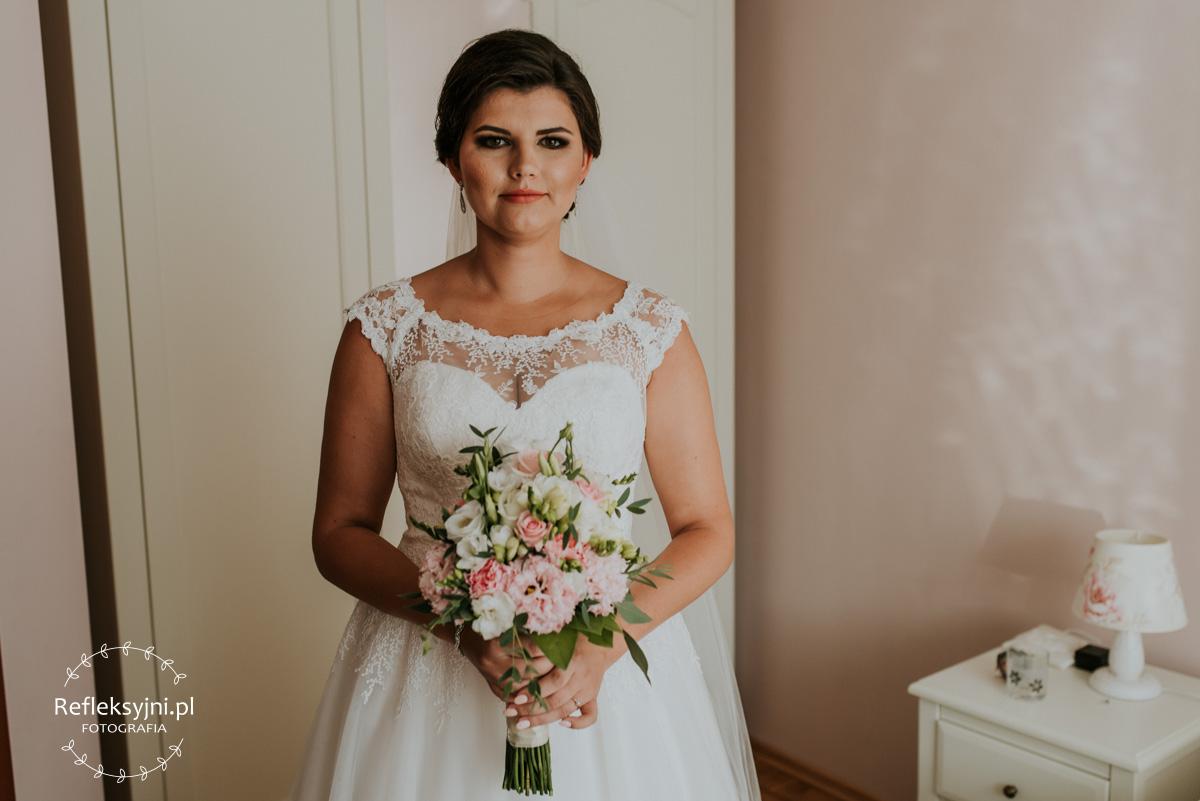 Pani Młoda stojąca z bukietem ślubnym
