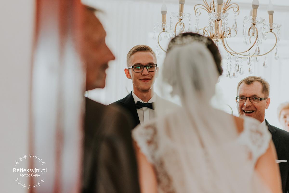 Zachwycony Pan Młody wraz z Ojcem pierwszy raz widzą Panią Młodą w sukni ślubnej