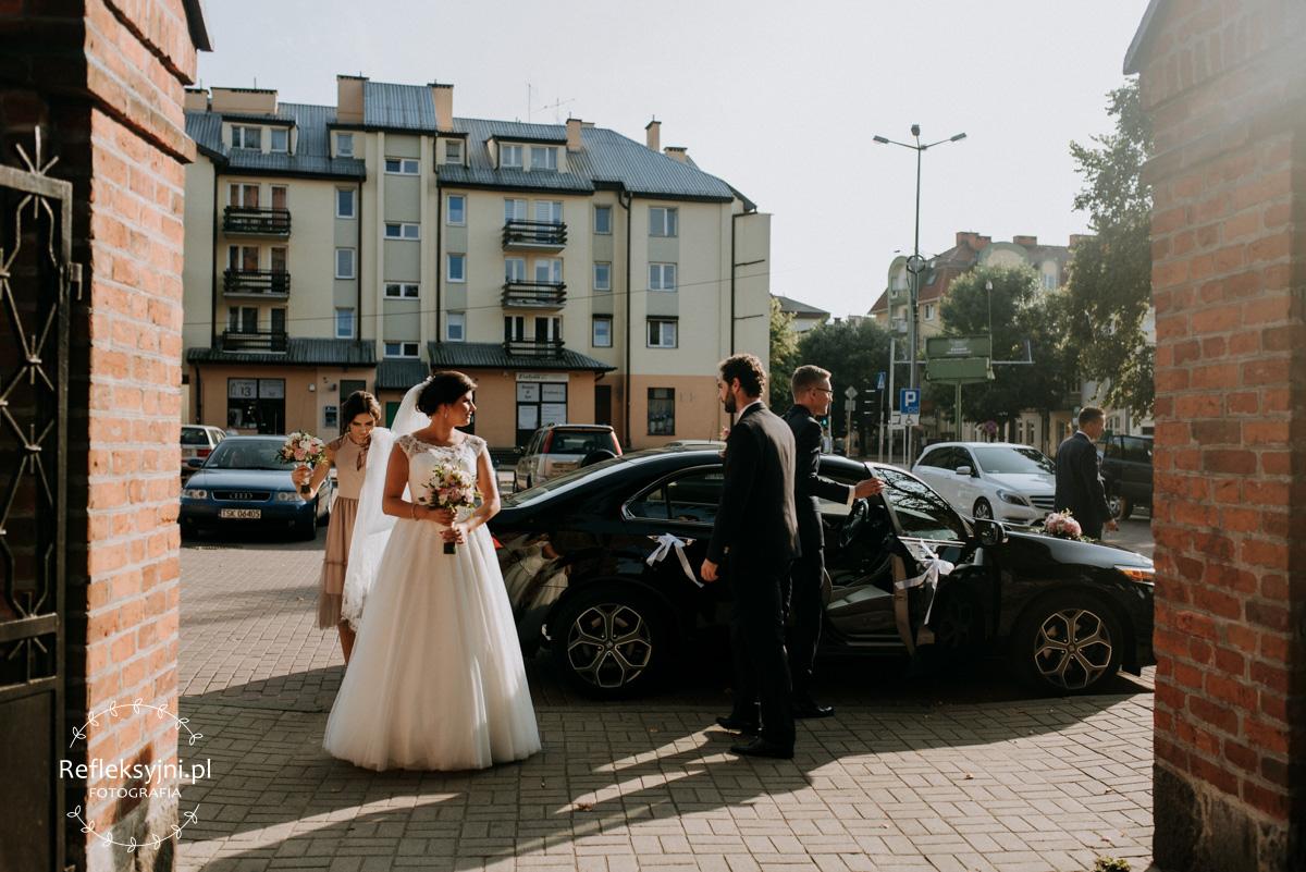 Pani Młoda stojąca obok samochodu