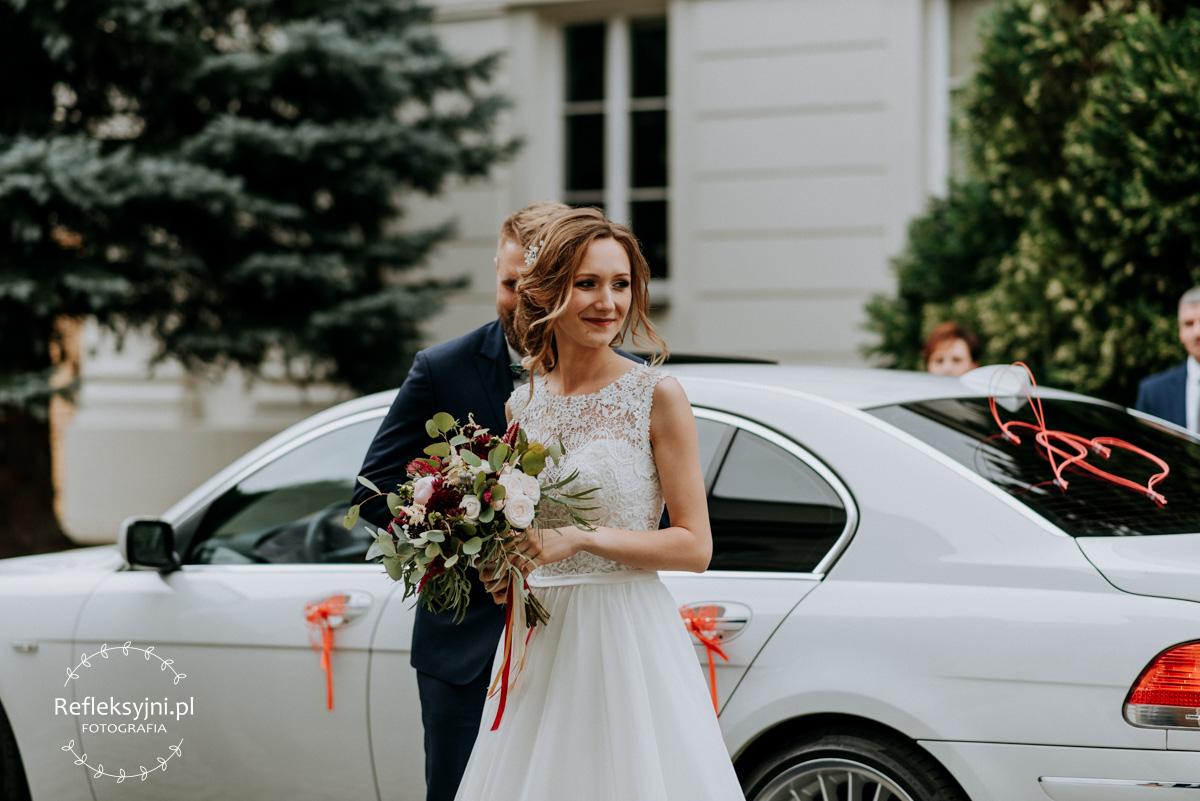 Państwo Młodzi wysiadają z samochodu weselnego