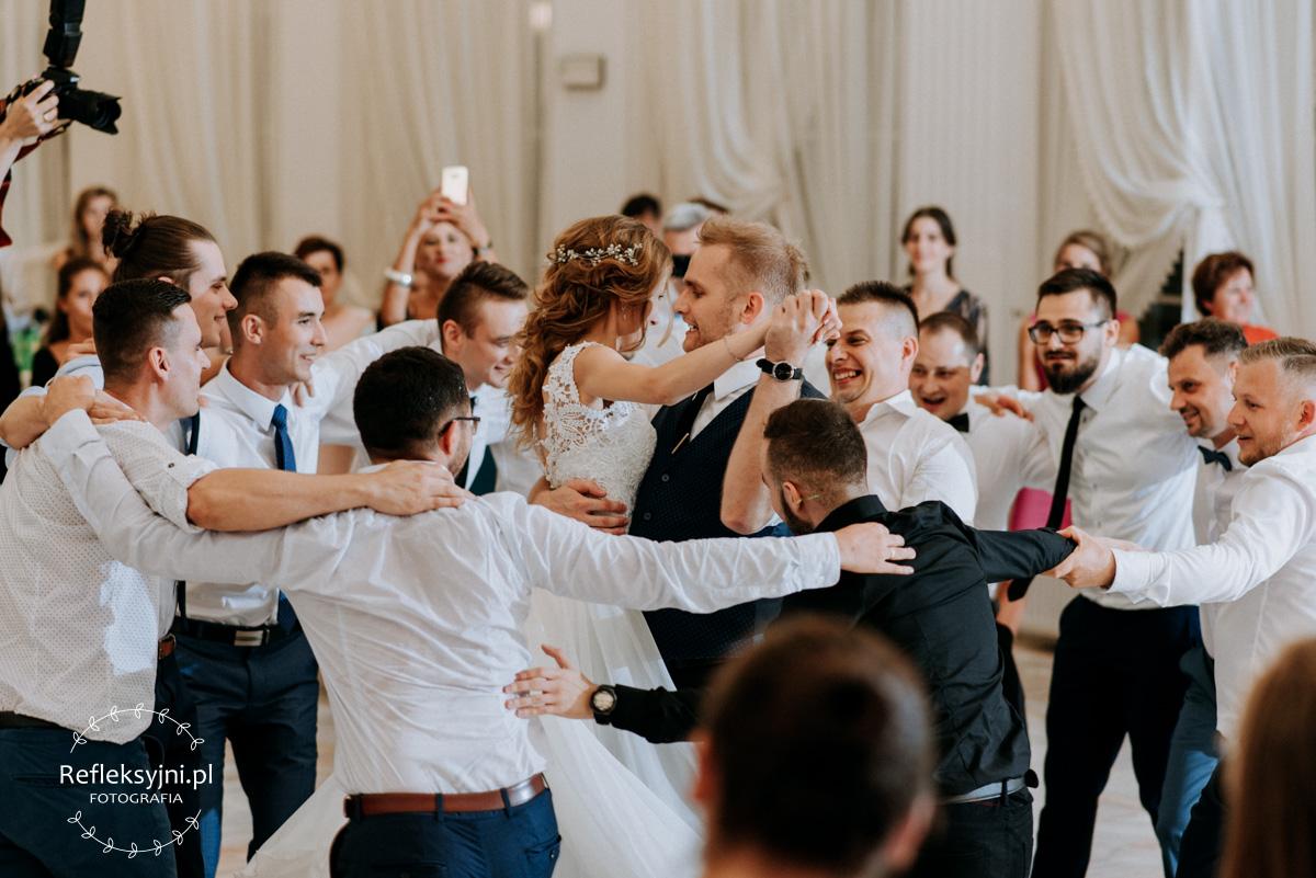Panowie tańczą w kółku wokół Pani Młodej